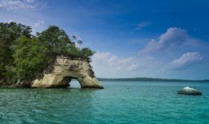 blue skies, water, small rock island