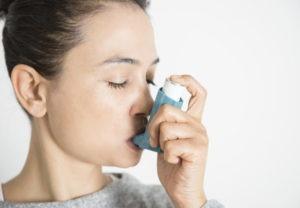 Young woman inhaling asthma inhaler, close-up.