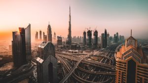 sunset skyline of dubai with skyscrapers and highway