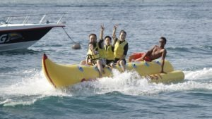 three adults two kids riding inflatable banana boat
