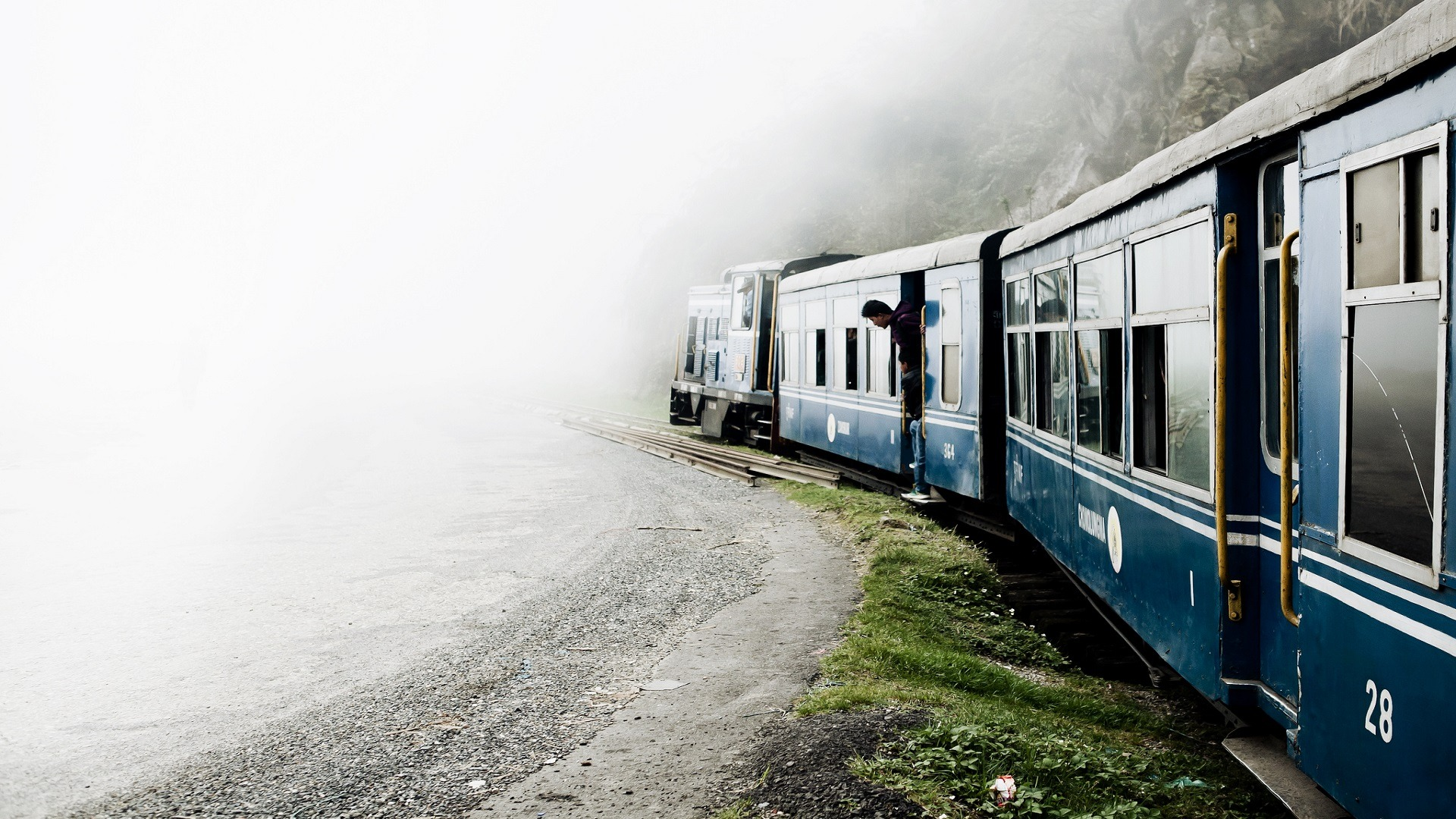 toy train travelling beside a hill through clouds