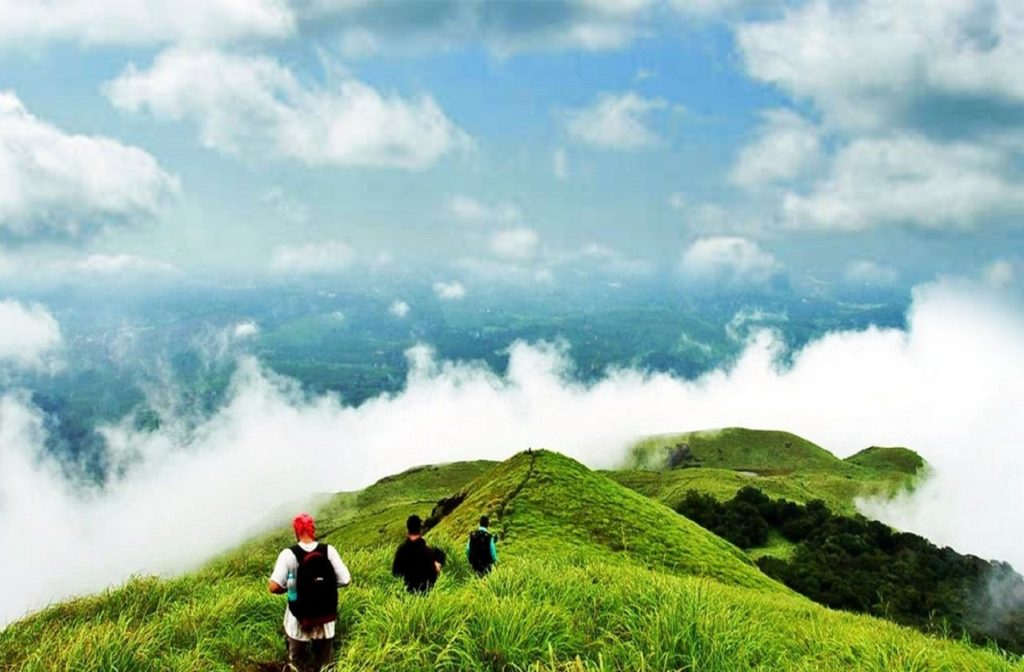 three people trailing the mountain covered with clouds