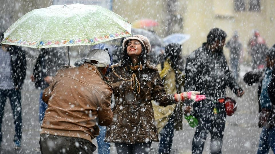 people enjoying snowfall in shimla