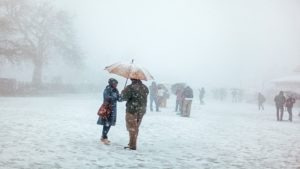 people standing under the snowfall