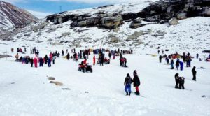 people skiing, people riding atv on the snowy mountain of himachal