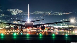 plane landing on airport with a light up city in the night