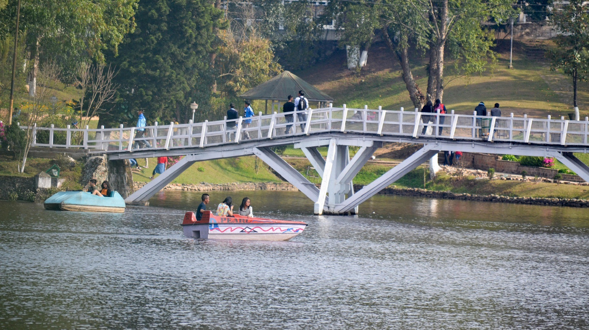people paddle boating on a pond and some people walking over the bridge