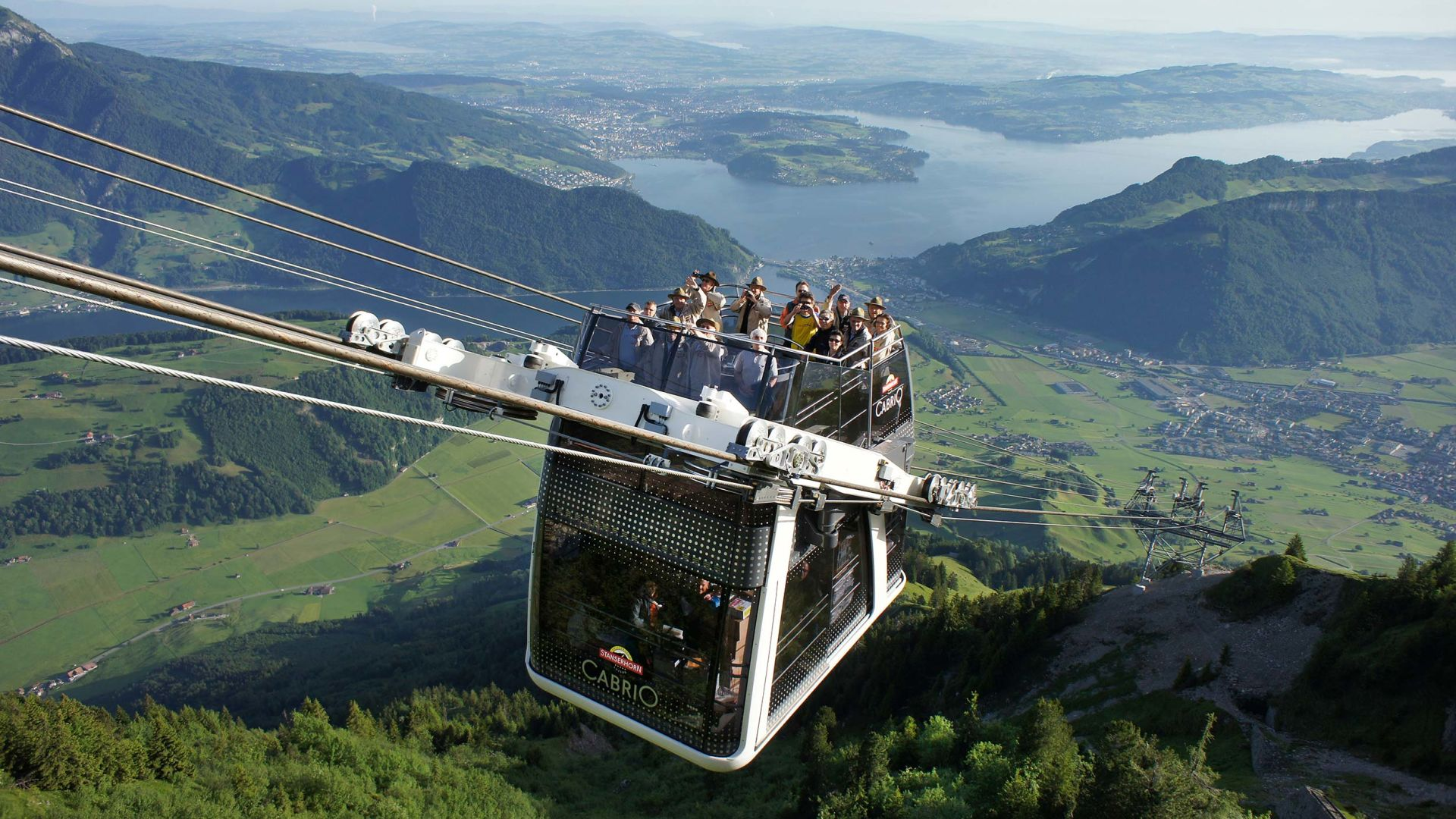 mountain cable car carrying people going up a mountain, view of lake and mountains