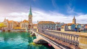 people on a bridge, waterbody, church beside buildings