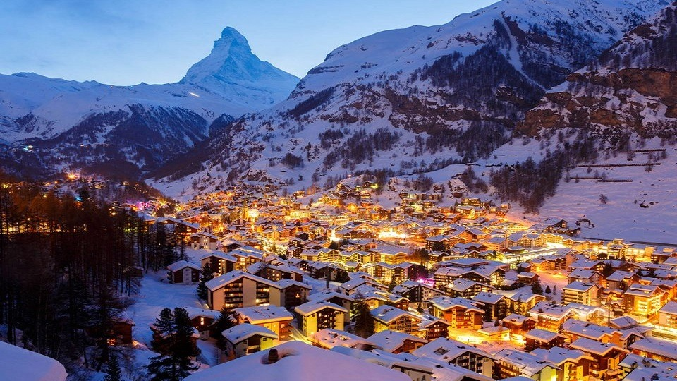 mountain covered with snow, a small town in evening