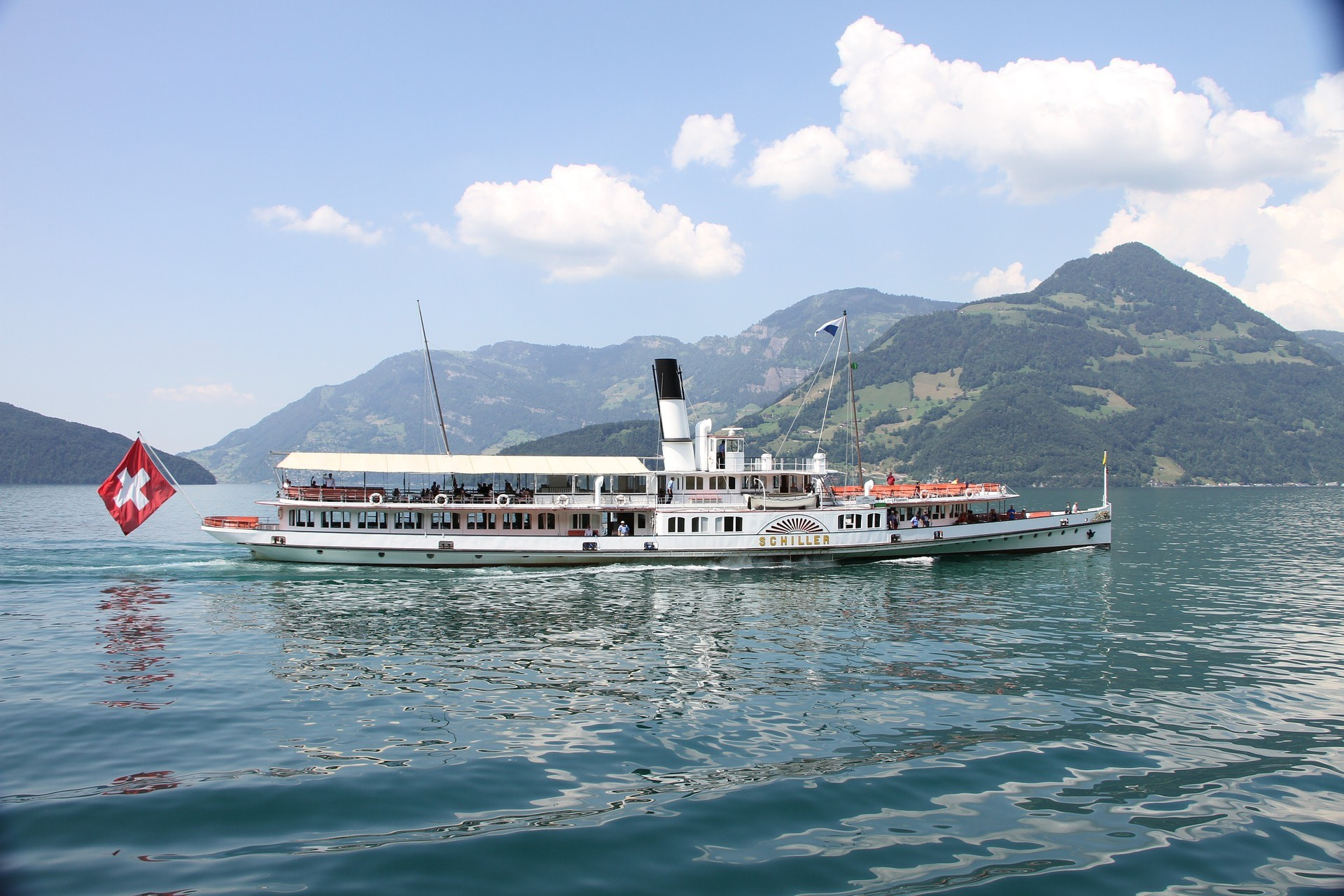 ferry boat in water travelling, mountains