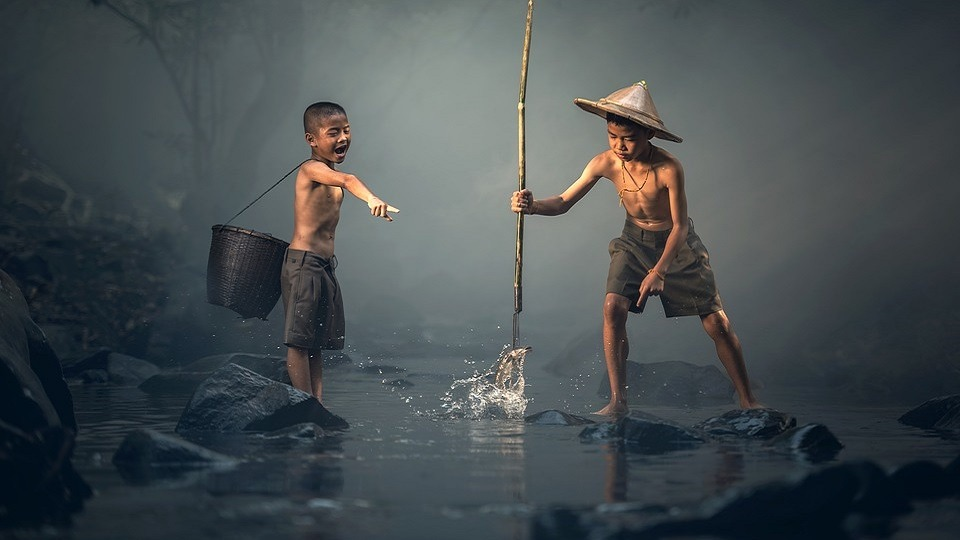 two boys fishing in a river