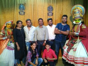 group of people taking picture with kathakali dancers