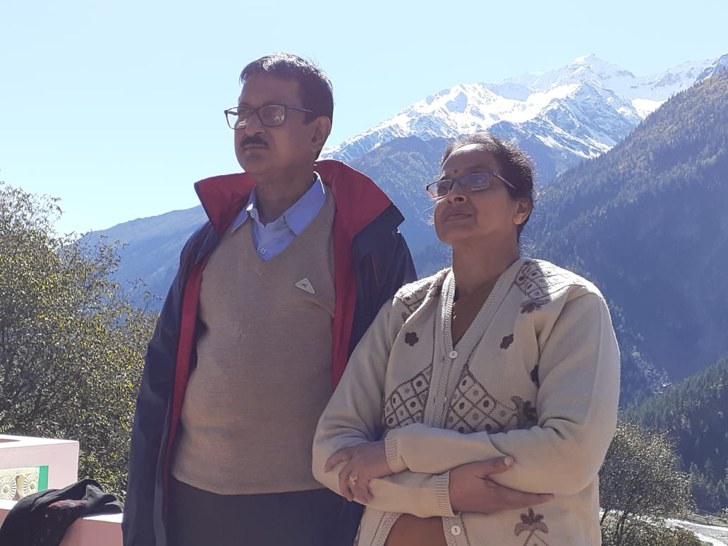 a couple posing with ice covered mountain in the background